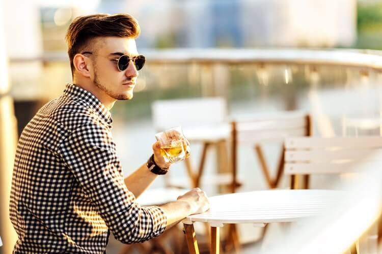 modny młody mężczyzna siedzi przy stoliku ipije whisky