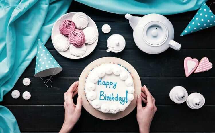 tort urodzinowy, ciastka i imbryk z herbatą na stole z ciemnego drewna widok z góry
