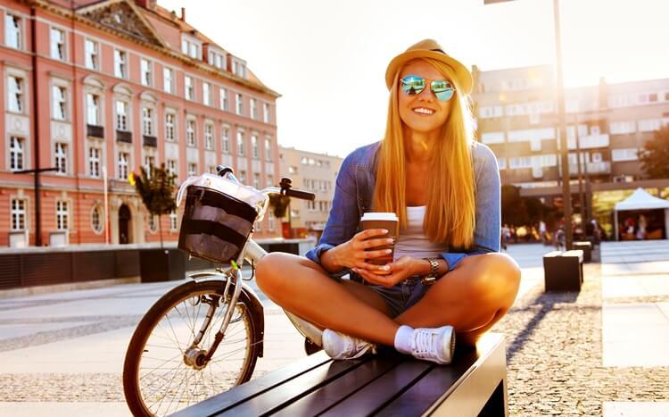 młoda modnie ubrana kobieta z kawą i rowerem siedzi na ławce na starym mieście