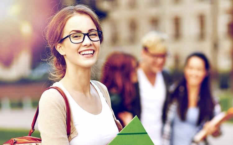 szczęśliwa studentka zzieloną teczką chodzi pokampusie