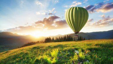 zielony balon na ogrzewane powietrze leci w górach na tle zachodu słońca