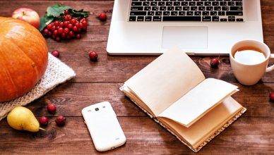 widok z góry na biurko z laptopem, dynią, telefonem, książką i kubkiem herbaty