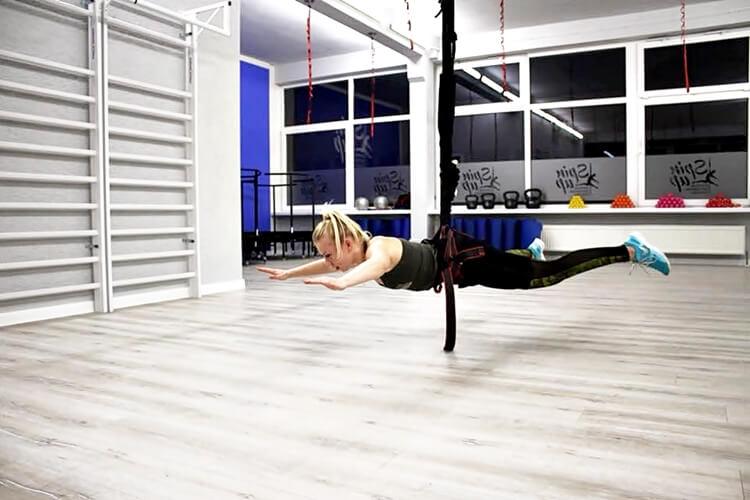 kobieta wisi zawieszona nad podłogą na linie bungee fitness