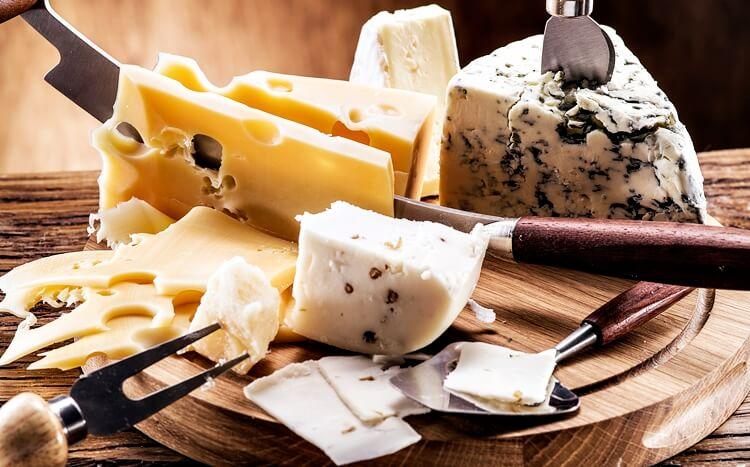 różne gatunki sera ułożone nadrewnianej desce
