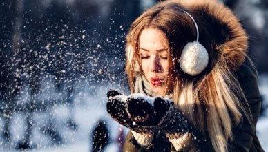 młoda kobieta zdmuchuje śnieg z wełnianych rękawiczek