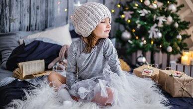mała dziewczyna siedzi na łóżku na tle choinki i świątecznych prezentów