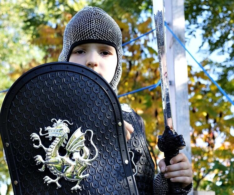 dziecko w zbroi rycerskiej z tarczą i mieczem