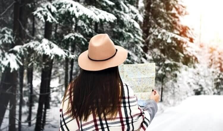kobieta zimą w lesie trzyma w rękach mapę widok tyłem,