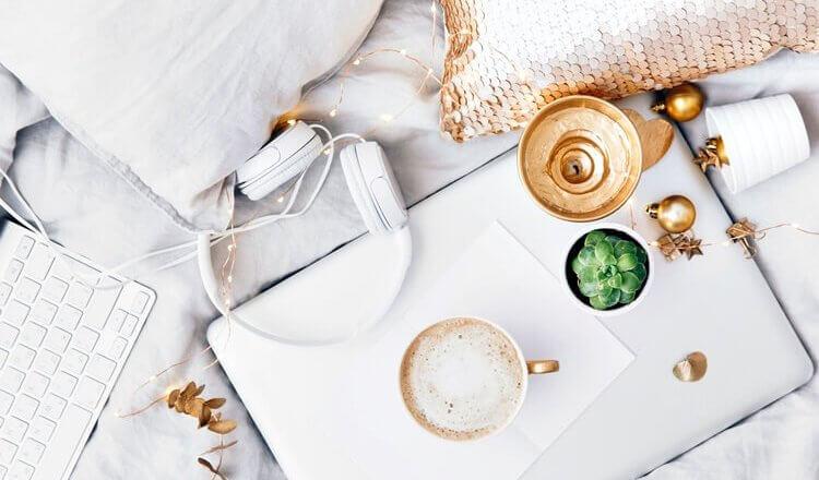 laptop, kawa i słuchawki na łóżku widok z góry