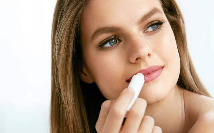 piękna kobieta smaruje usta pielęgnacyjnym balsamem ochronnym w sztyfcie