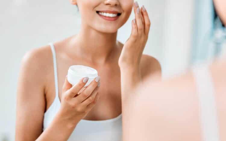 młoda kobieta nakłada krem na skórę twarzy