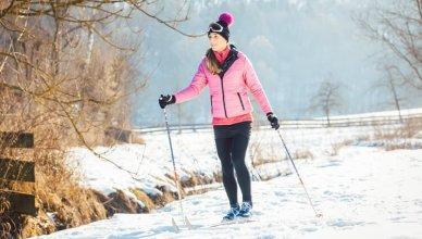 młoda kobieta na nartach biegowych w lesie