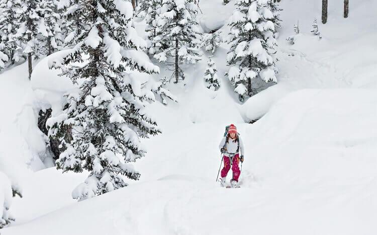 kobieta na nartach wychodzi pod górę poza szlakiem