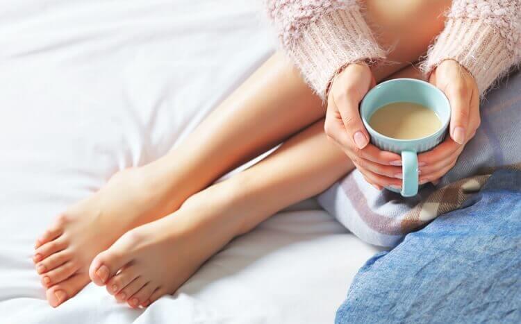 zadbane kobiece stopy i dłonie z kubkiem kawy