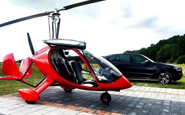 czerwony wiatrakowiec z zabudowaną kabiną pilota stoi na parkingu obok czarnego suva