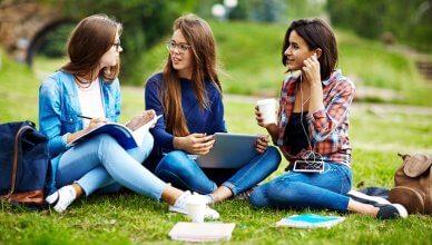 trzy koleżanki uczą się w parku