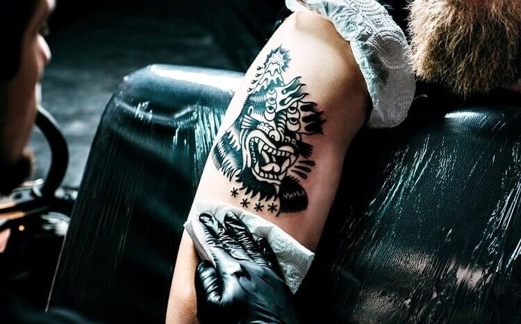 tatuażysta przeciera gotowy tatuaż na ramieniu mężczyzny