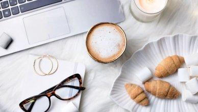 laptop, kawa, okulary, rogaliki i świeca widok z góry