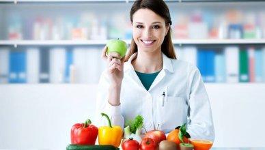 młoda kobieta dietetyk uśmiecha się w gabinecie trzymając w ręku jabłko