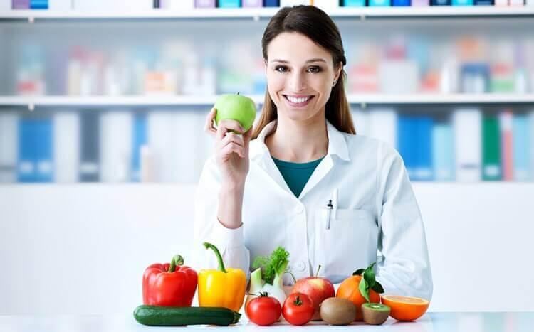 młoda kobieta dietetyk uśmiecha się wgabinecie trzymając wręku jabłko