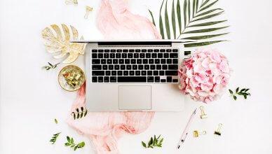 laptop na różowej chustce w otoczeniu różowych hortensji i zielonych listków widok z góry