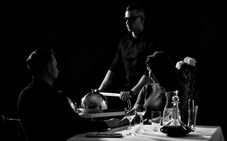 para wciemnej restauracji obsługiwana przezniewidomego kelnera