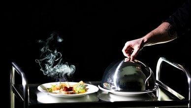 stolik z gorącym parującym posiłkiem na ciemnym tle