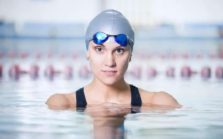 kobieta w stroju kąpielowym, czepku i okularkach pływackich stoi w basenie