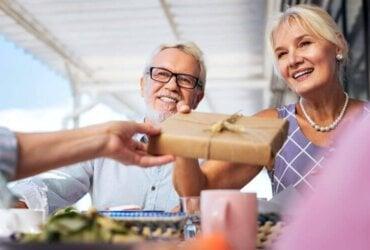 Uśmiechnięci starsi ludzie przyjmujący prezent