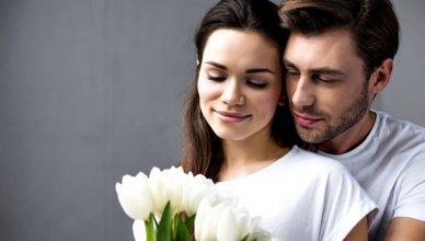 mężczyzna przytula kobietę, która trzyma bukiet białych tulipanów