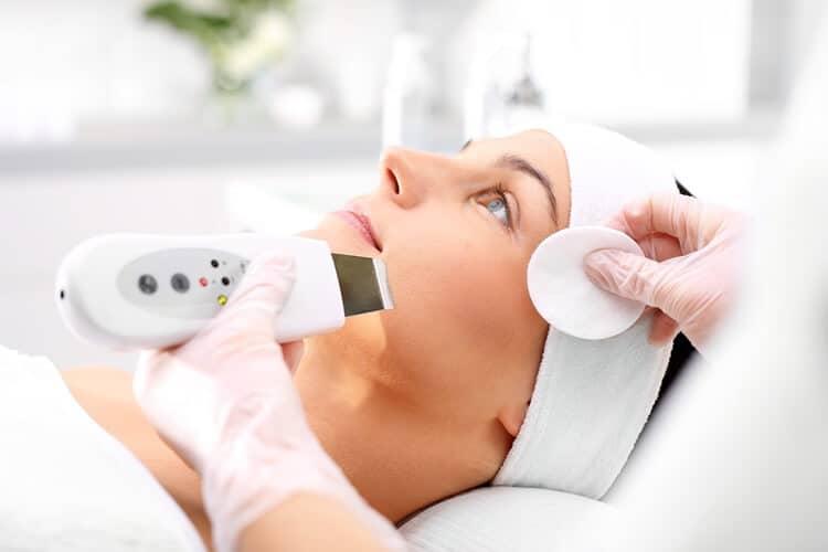 kosmetolog przeprowadza peeling kawitacyjny na twarzy kobiety