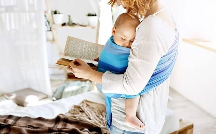 młoda kobieta nosi dziecko wchuście iczyta książkę