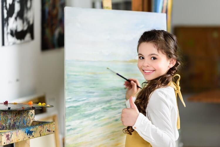 dziewczynka maluje obraz na zajęciach plastycznych