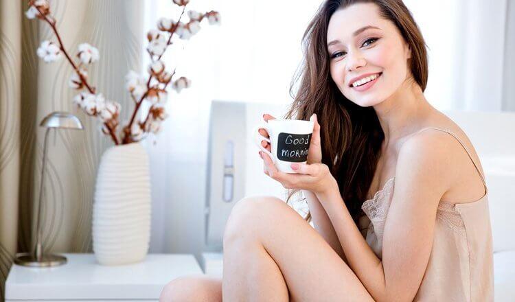 piękna młoda kobieta siedzi na łóżku z kubkiem herbaty