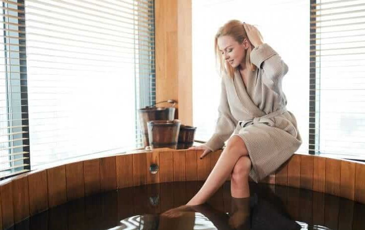 kobieta w szlafroku moczy nogi w drewnianej bali