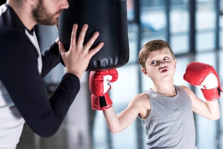 mały chłopiec trenuje boks podokiem trenera