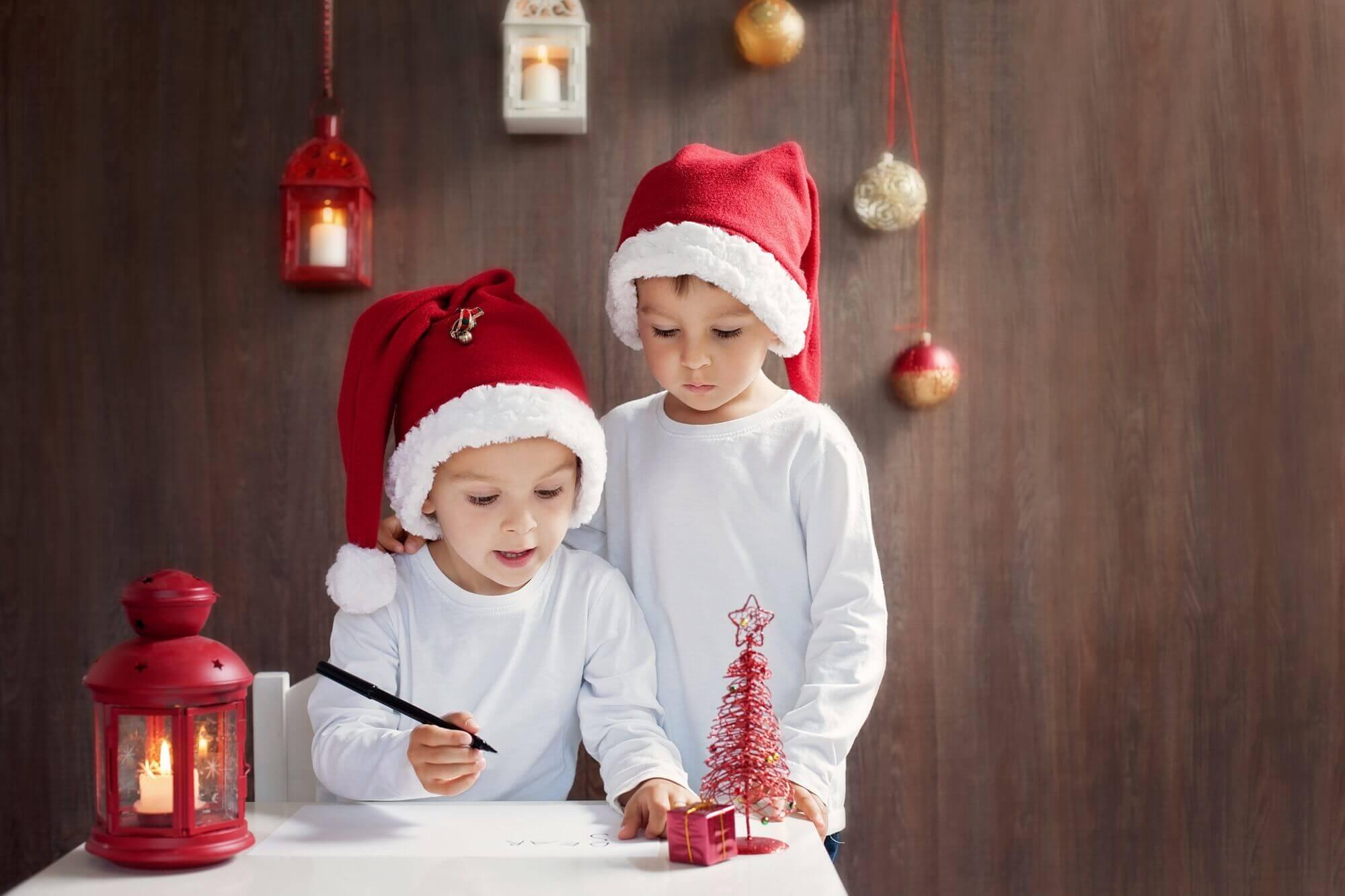 dwóch małych chłopców pisze list do świętego mikołaja