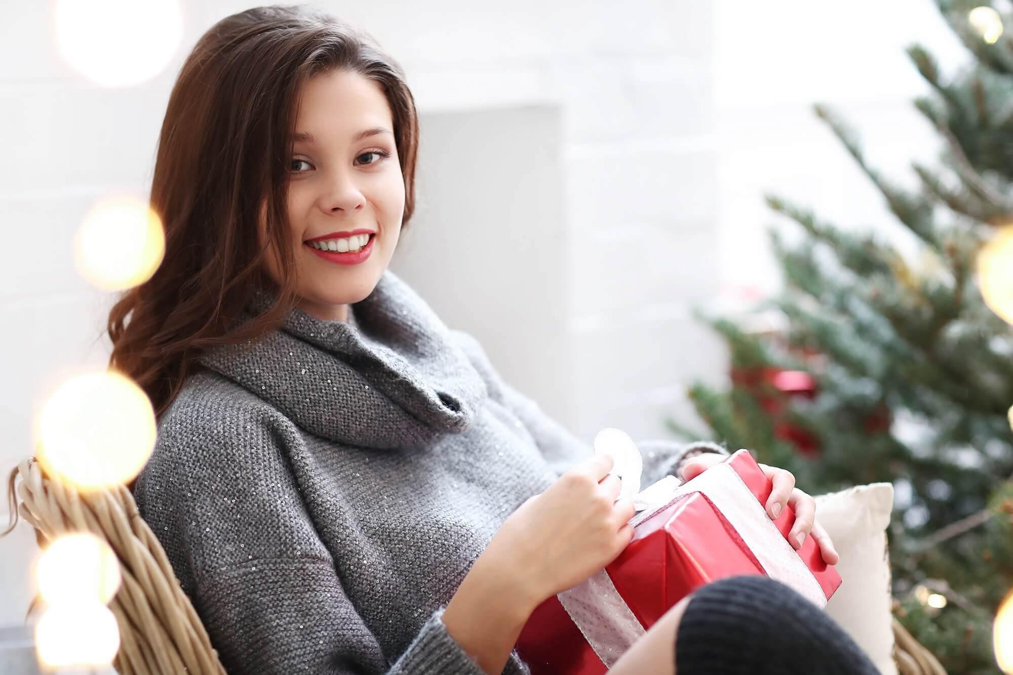 młoda dziewczyna rozpakowuje świąteczny prezent