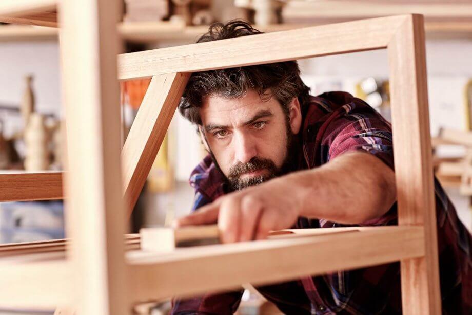 mężczyzna stolarz wykonuje drewniane krzesło