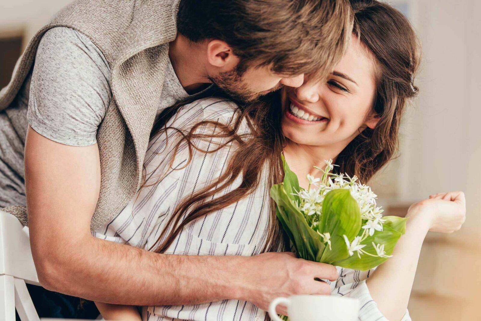 mężczyzna wręcza kobiecie kwiaty na prezent
