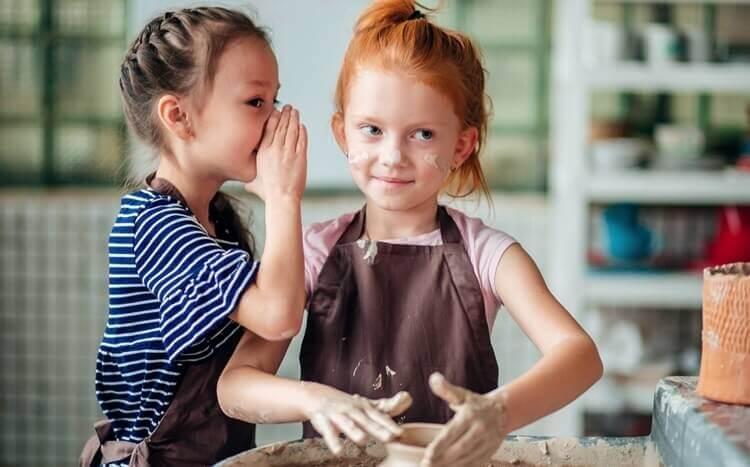 dwie dziewczynki nawarsztatach ceramicznych szepczą sobie coś doucha