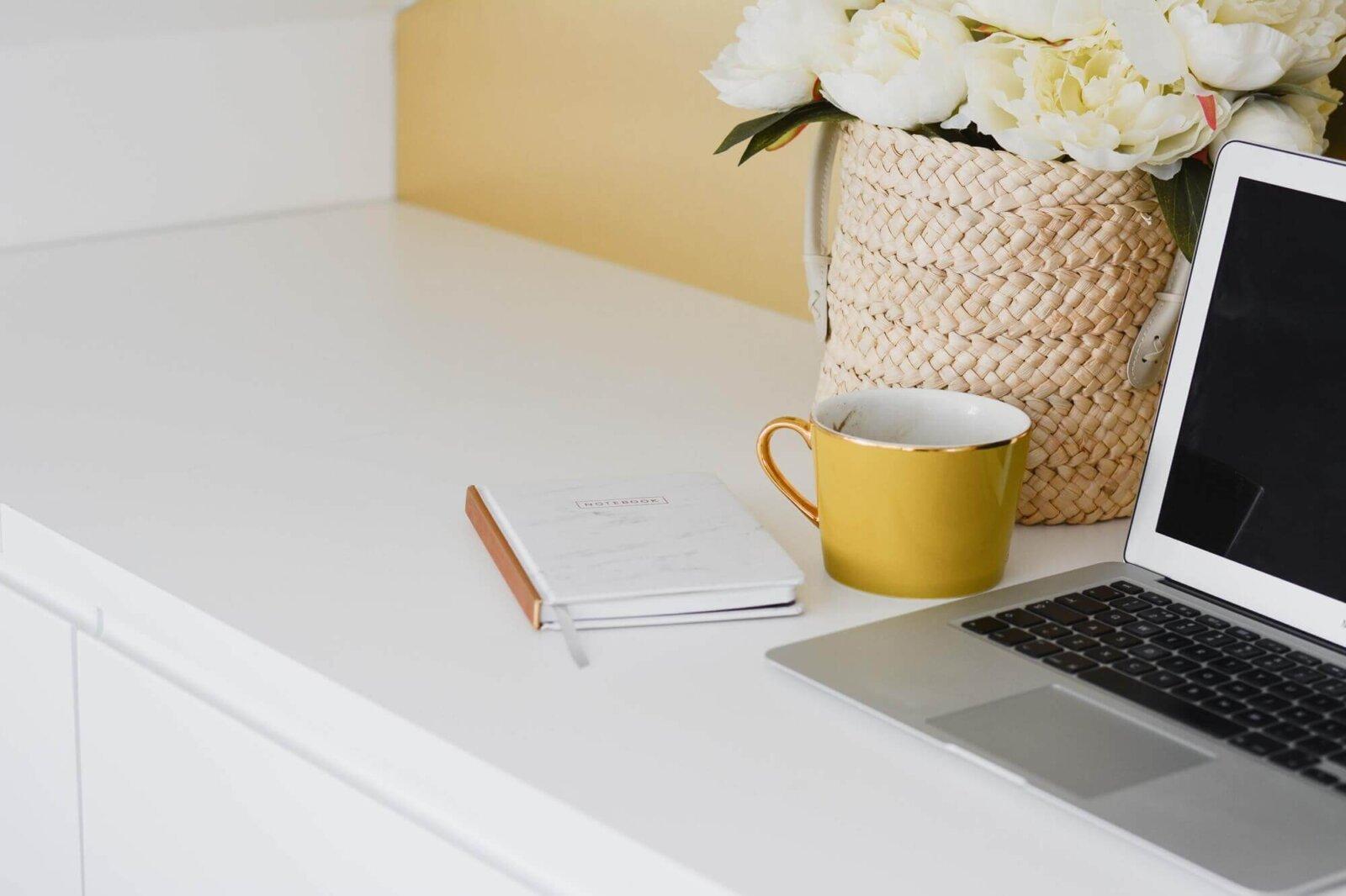 laptop, notes i kubek z kawą na biurku obok kosza kwiatów