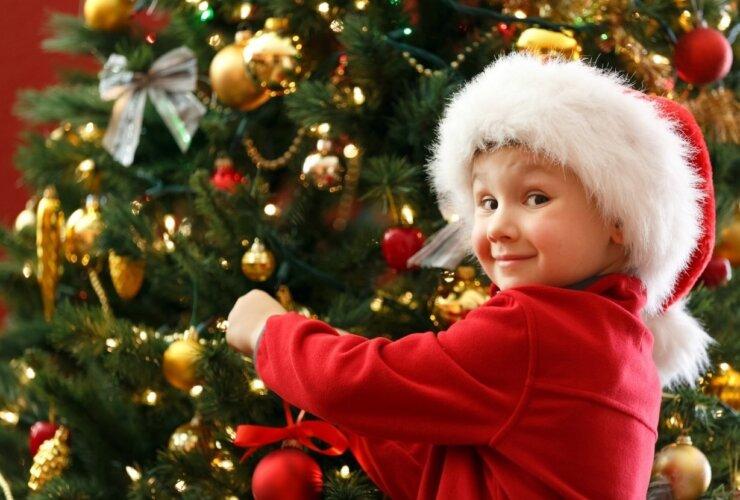 Dziecko w czapce Mikołaja ubierające choinkę