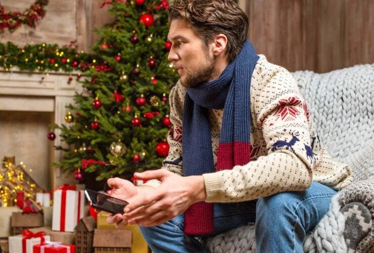 Mężczyzna trzymający w ręku telefon pośród świątecznych ozdób