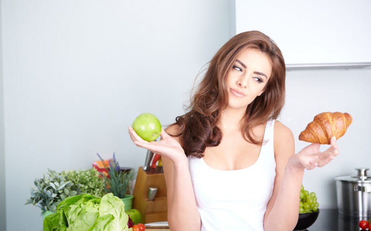 Kobieta zzastanawiającą się mimiką, trzymająca jabłko orazcroissanta