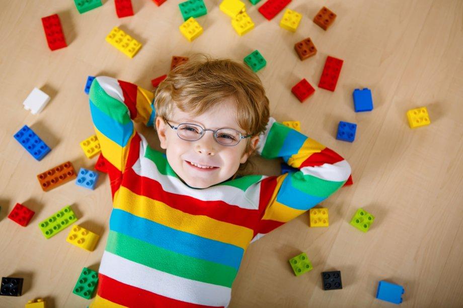 mały chłopiek wokularach zkolorowymi klockami