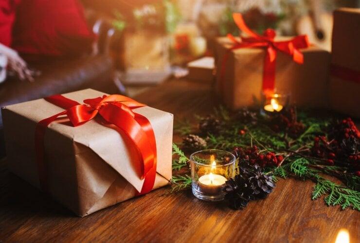 Prezenty na stole świątecznym pośród świec oraz ozdób